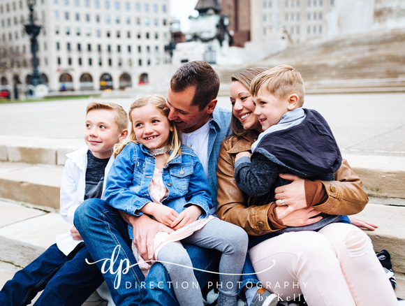 Attractive young family sitting on steps in front of Soldiers and Sailors Monument in Indianapolis IN
