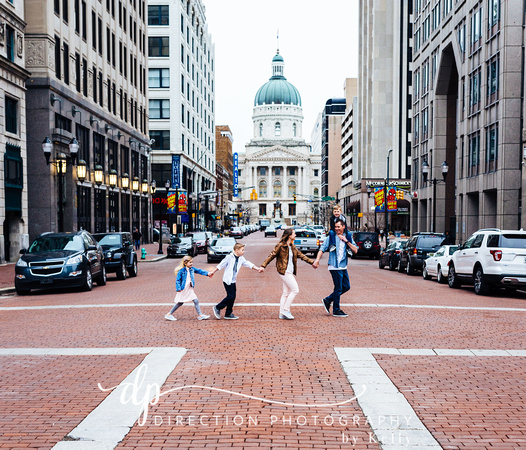 A family is crossing the street in downtown Indianapolis with the Indiana State Capital Building in the background.