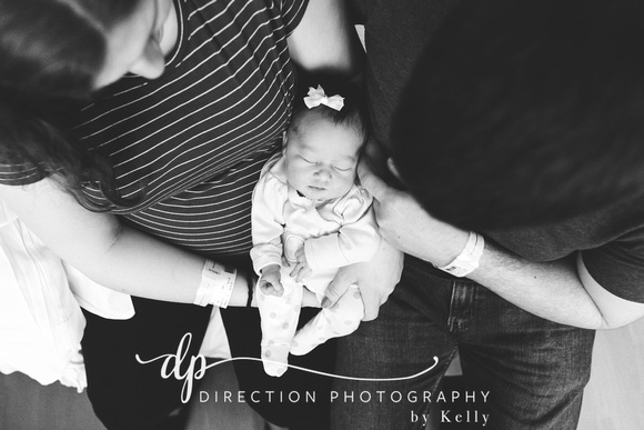Newborn baby MacKenna being held in her Mom and Dad's arms
