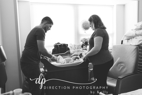Mom and Dad changing the diaper of their newborn daughter MacKenna