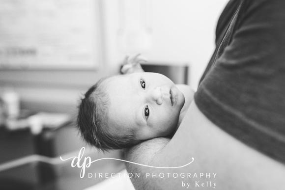 Newborn baby MacKenna sleeping in her Dad's arms