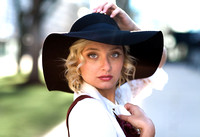 High school senior girl with curly blond hair wearing a floppy black hat posing for her senior portrait session