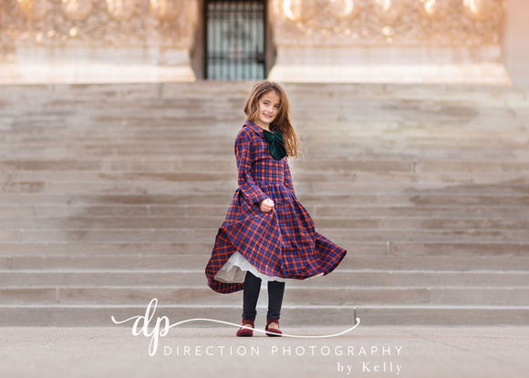 Young girl model in a long red and blue plaid dress