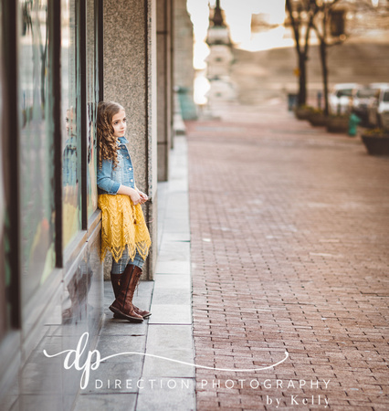 Young fashion model wearing jean jacket, yellow skirt and boots posing in downtown Indianapolis Indiana