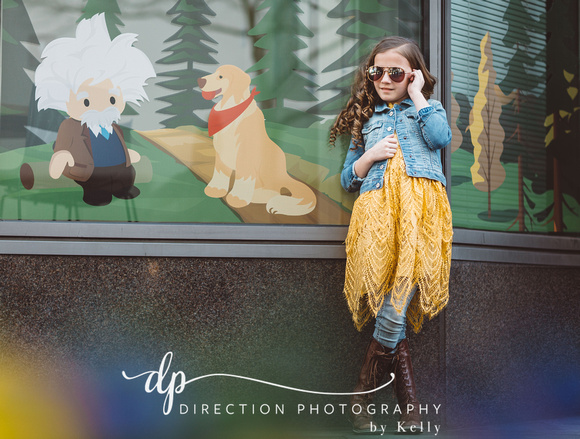 Young fashion model wearing jean jacket, yellow skirt, boots and sunglasses