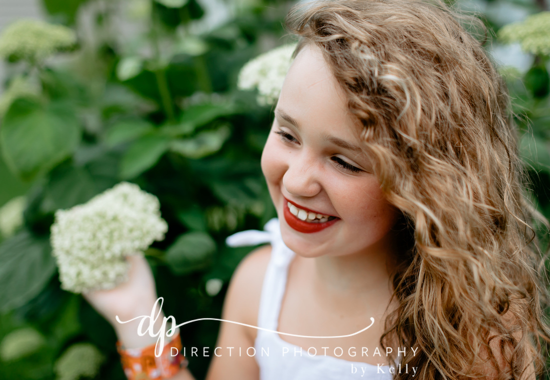 Young girl holding a white hydrangea flower as she looks to the side with a big smile.