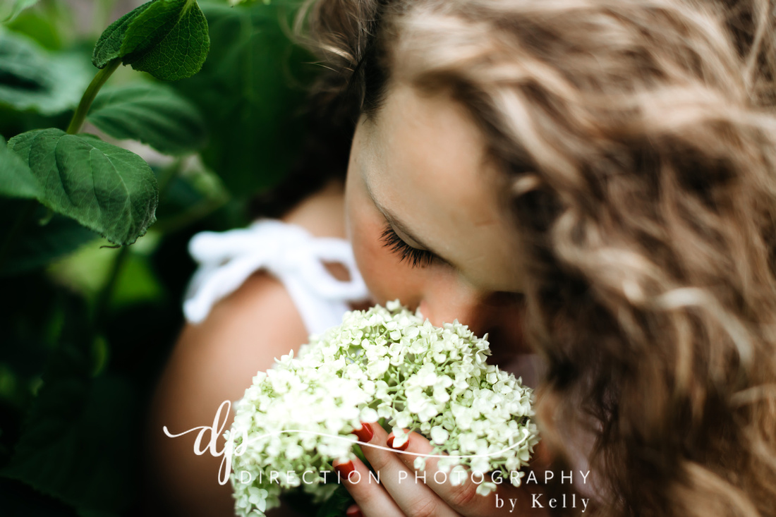 Young girl wearing a white dress sniffing white hydrangeas.