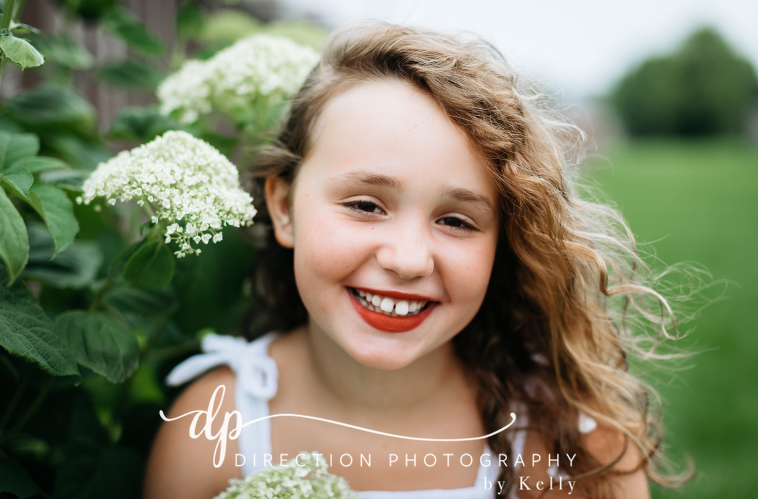 Nine year old girl wearing red lipstick smiling sweetly as she sits in front of white hydrangeas.