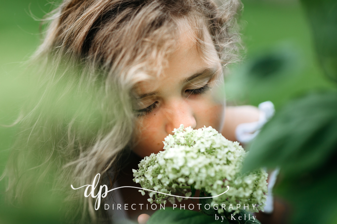 A young girl smells a white hydrangea as she peers at the flower.