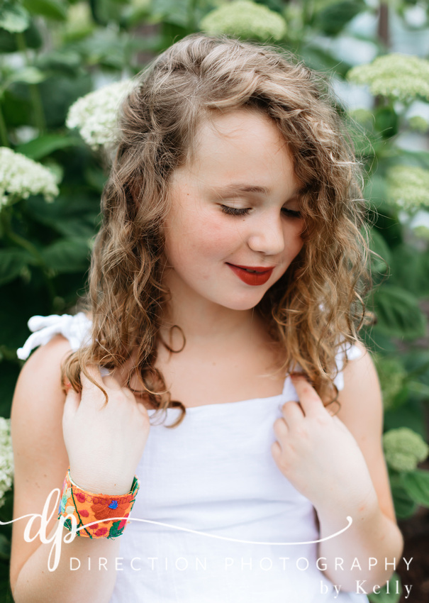 A young girl with long wavy hair plays with the ends of her hair as she wears a white dress and embroidered bracelet from Texas.
