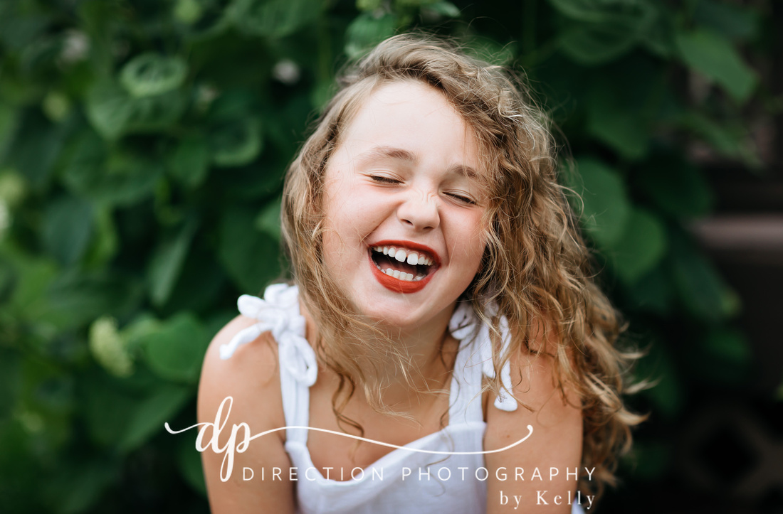 A young girl laughs as she sits in the grass on a beautiful summer day