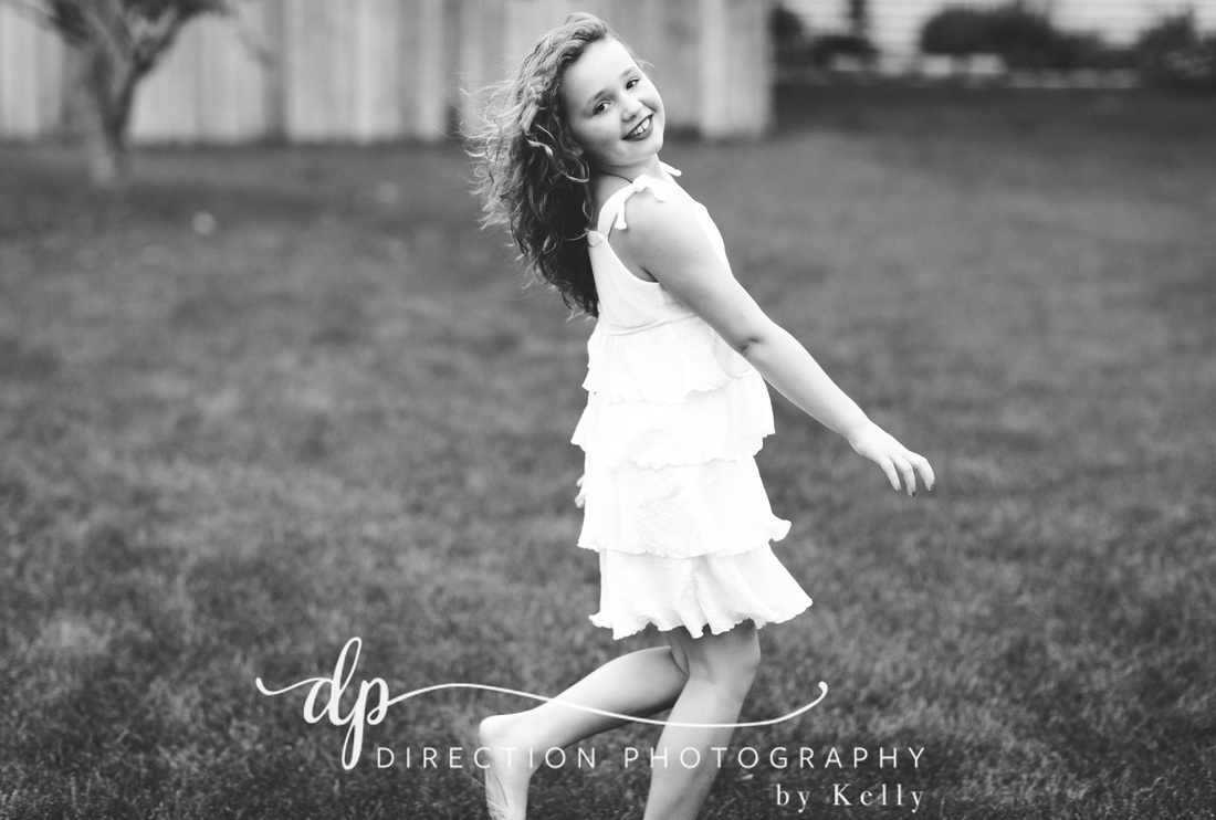 A black and white photo of a girl looking over her shoulder as she twirls barefoot in the grass.