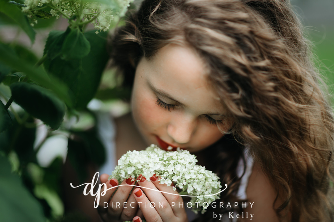 A young girl wearing bright red lipstick and red nail polish holds a white hydrangea as she enjoys the sweet aroma.