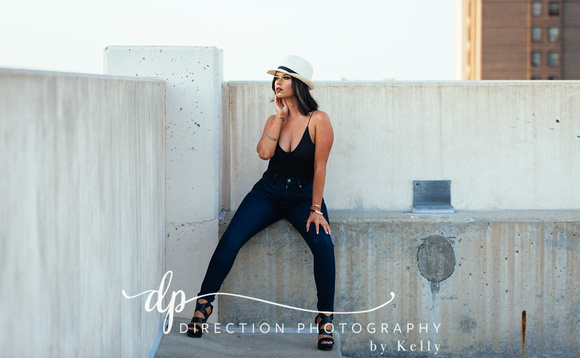 Fashion shoot of a model looking over the ledge of a rooftop parking garage in Rockford IL